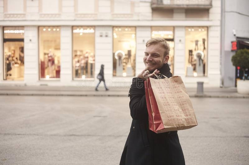 One young smiling man, rear view, 20-29 years old, standing on a pedestrian street in city, looking, while holding two shopping. Bags on his back. Store front stock images