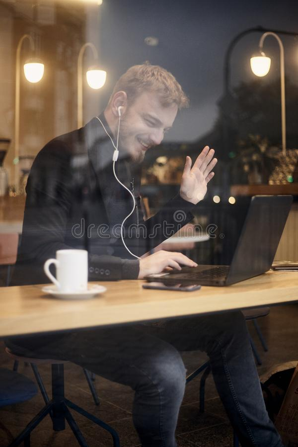 One young smiling man, sitting in coffee shop and using his laptop, gesturing with his hand Hello or Hi, waving his hand over. Video conference call. Shoot royalty free stock photos