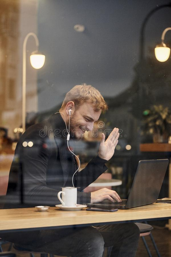 One young smiling man, sitting in coffee shop and using his laptop, gesturing with his hand Hello or Hi, waving his hand over. Video conference call. Shoot stock photo