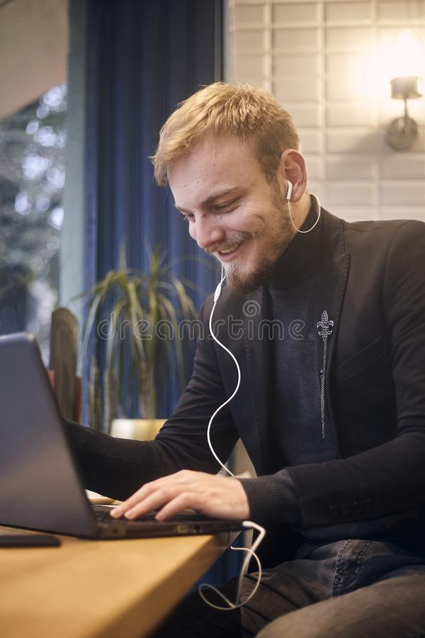 One young smiling man, sitting indoors in coffee shop and using his laptop, earbuds in ear.  stock photos
