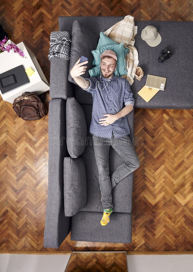 One young smiling man, talking selfie with his smart-phone, laying in sofa. view from above of his whole room, full lenght shot. One young smiling man, talking stock photos