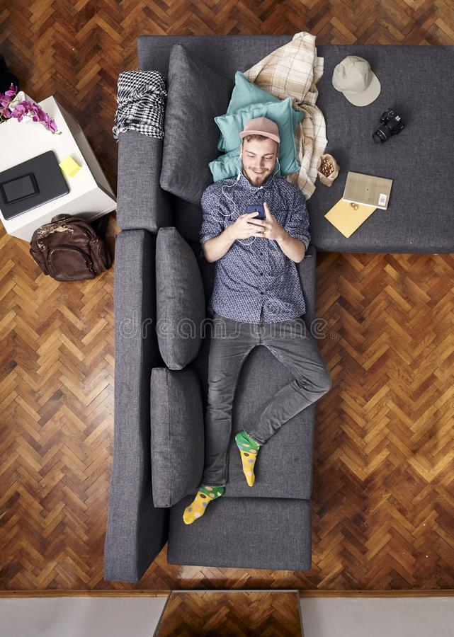 One one young smiling man, using smart-phone while laying in sofa. view from above of his whole room, full lenght shot. One one young smiling man, using smart stock images