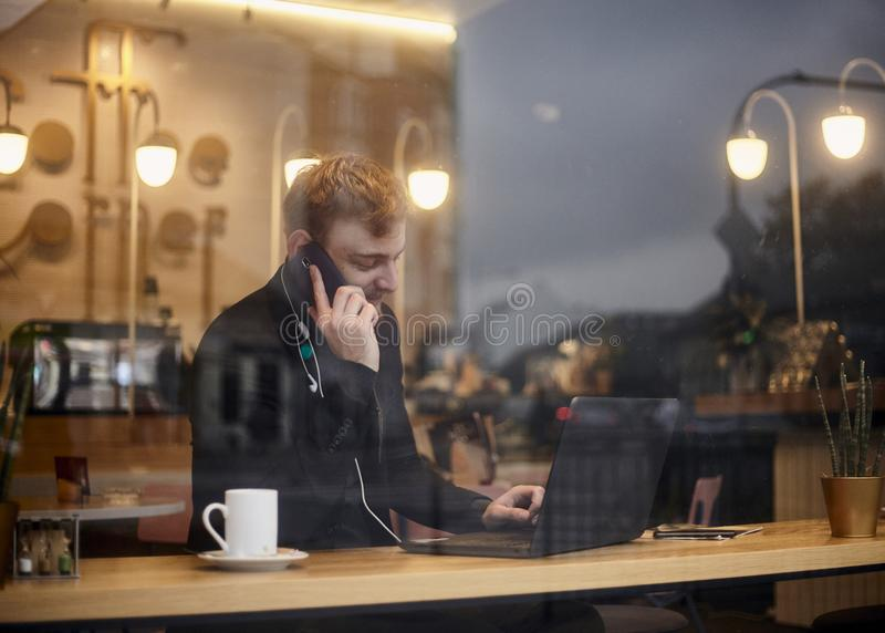 One young smiling man, 20-29 years, sitting in coffee shop and using, his laptop while talking over phone. Shoot thought window. Outside with reflections from royalty free stock image