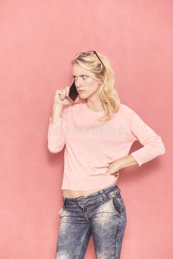 One young woman can not believe what is she hearing, over her phone, stock photo