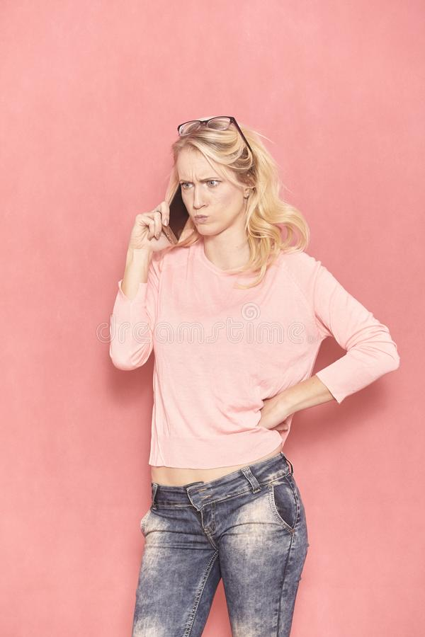 One young woman, funny yet angry face expression while talking over phone, stock photos