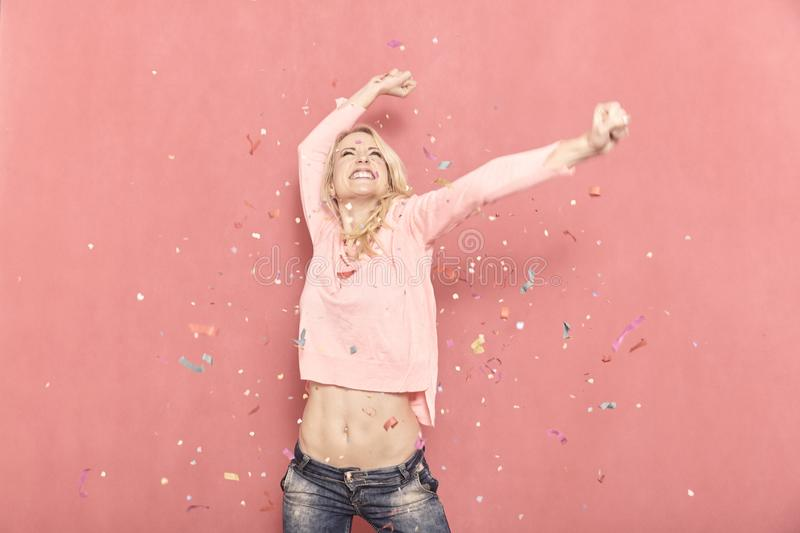 One young woman happy with arms outstreched high in air with confetti thrown, 20-29 years old, long blond hair. stock images
