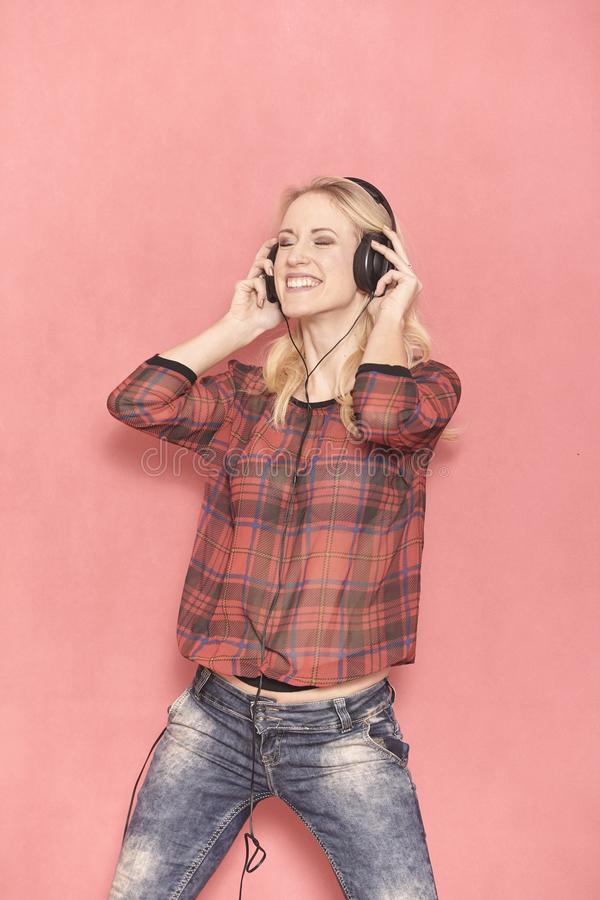 One young woman, hilarious laughing emotion, hilarious listening to music on headphones. royalty free stock photography