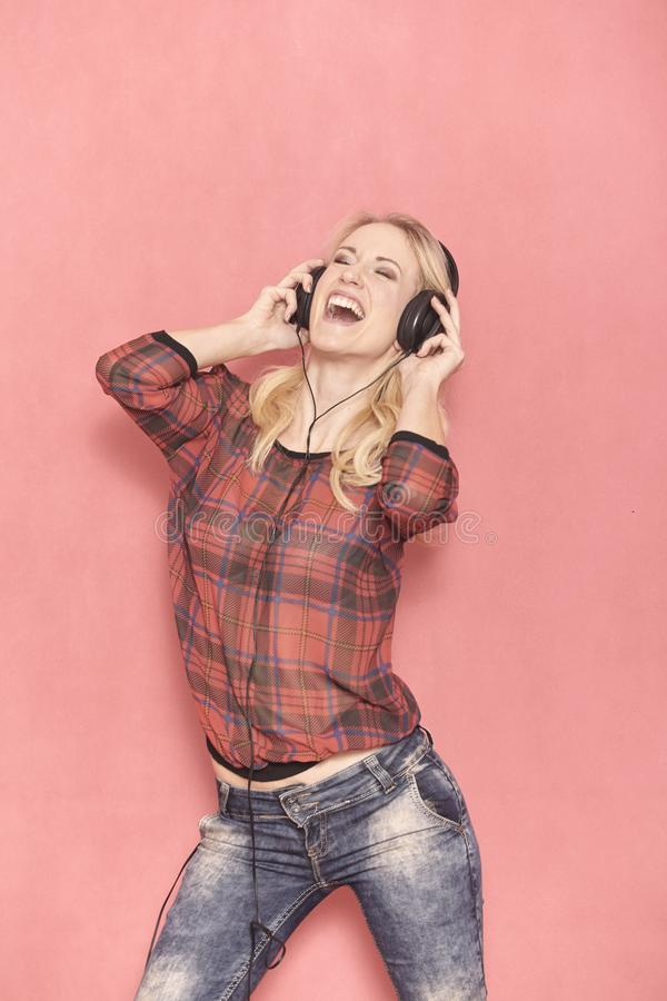 One young woman, hilarious laughing emotion, shouting while listening to music on headphones stock photo