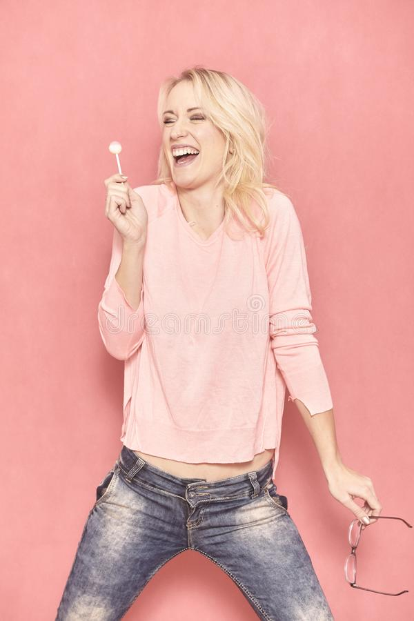 One young woman, laughing to the lollipop, royalty free stock image