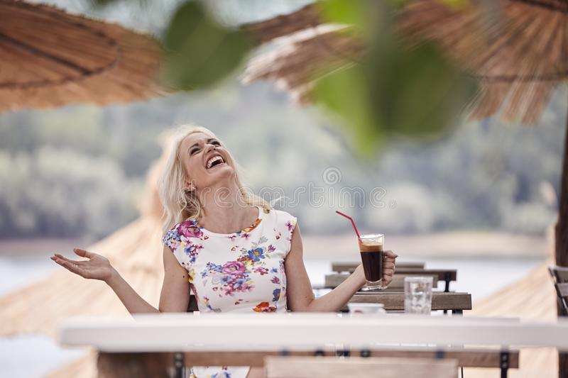 One young woman laughing, 25 years old, looking up above, sitting in beach cafe, drinking coffee from cup. royalty free stock photo