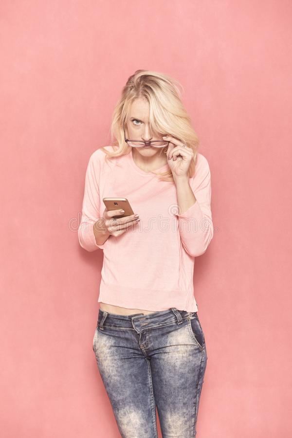 One young woman looking forward to camera, holding smart phone in her hand stock image