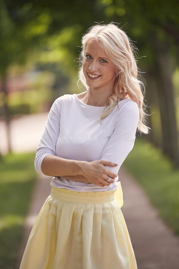 One young woman portrait, 25 years old, yellow dress, white top, park, smiling happy.  royalty free stock image