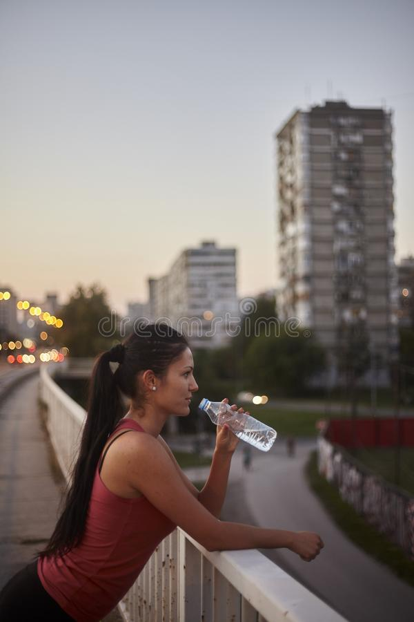 One young woman upper body, standing on a high ground, drinking water from bottle. Side view. Urban area, city buildings in background, out of focus stock images