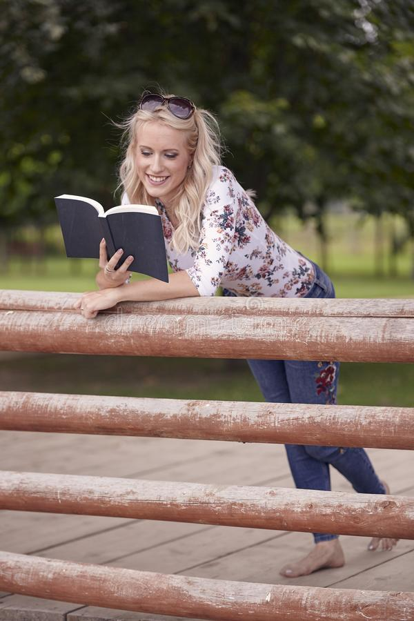One young woman, 25 years old, leaning on wooden fence in park. reading a book outdoors, happy smiling royalty free stock photography