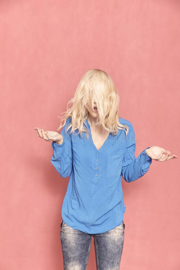 One young woman, 20-29 years old, messy chaotic long blond hair, almost hilarious since her face can `t be seen, arm`s raised in d royalty free stock photography