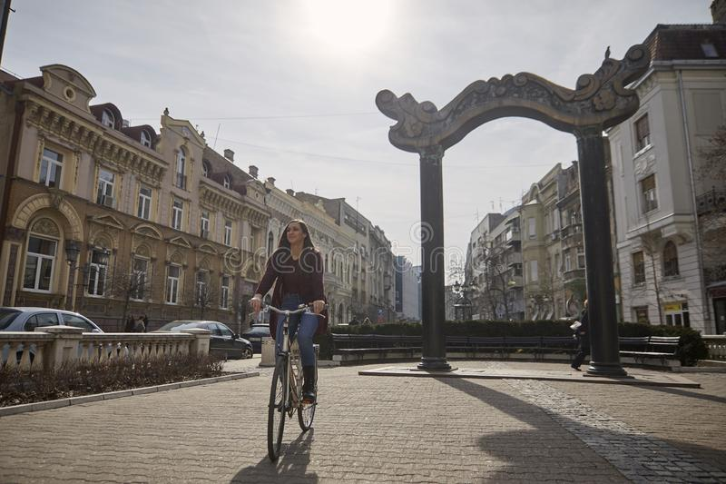 One young woman, 20-29 years old, riding a retro old bicycle on a old city European square. Smiling, happy royalty free stock photos