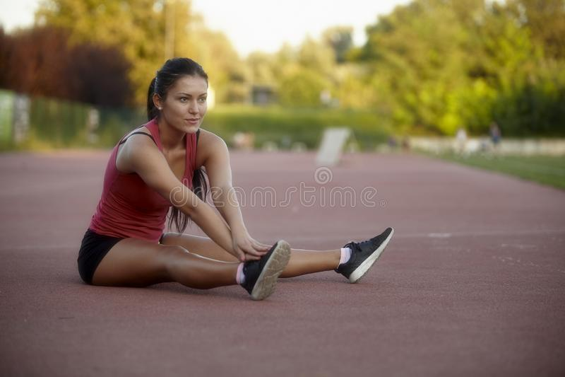 One young woman, 20-29 years, sitting on ground red tartan, stretching upper body and legs.  royalty free stock images