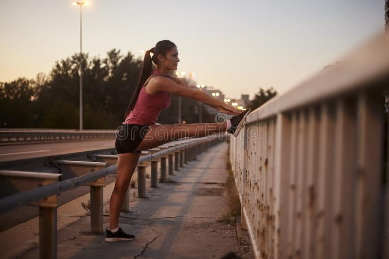One young woman, 20-29 years, stretching legs alone on a bridge. night time, sunset royalty free stock image