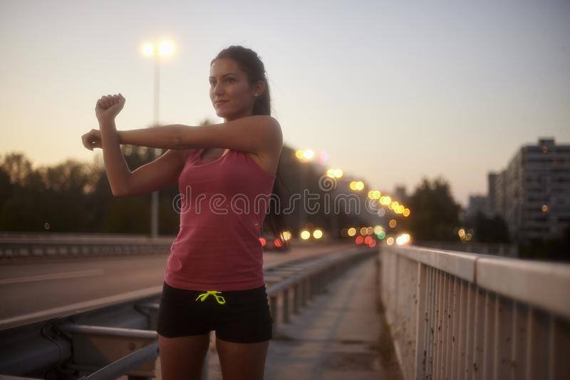 One young woman, 20-29 years, upper body shot, smirking while stretching arms outdoors on a bridge. stock photo