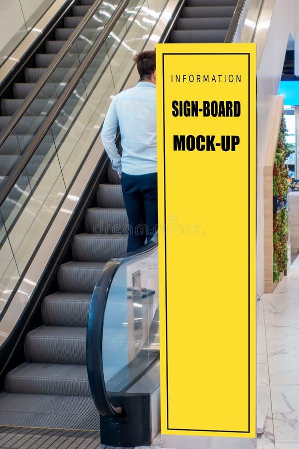 Onecht omhoog lang uithangbord dichtbij roltrap in winkelcomplex royalty-vrije stock fotografie