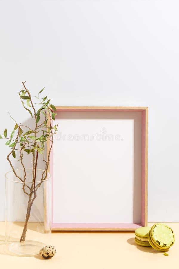 Onechte omhoog witte kader en tak met groene bladeren in blauwe vaas op boekenplank of bureau Minimalisticconcept royalty-vrije stock foto's