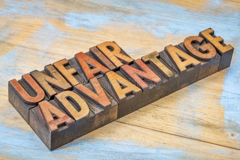Oneerlijk voordeel in letterzetsel houten type stock foto
