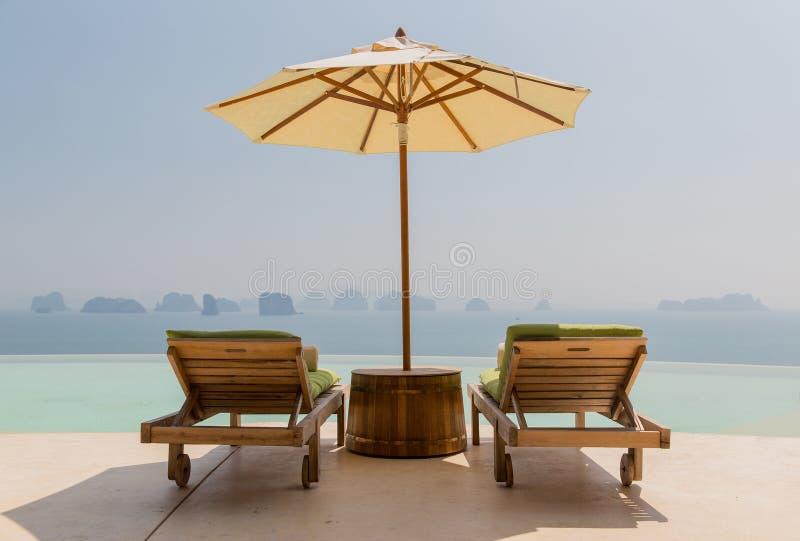 Oneindigheidspool met parasol en zonbedden bij kust royalty-vrije stock afbeeldingen