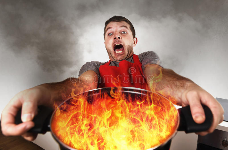 Onervaren huiskok met de pot van de schortholding het branden in vlammen met het gezichtsuitdrukking van de spanningspaniek stock foto's