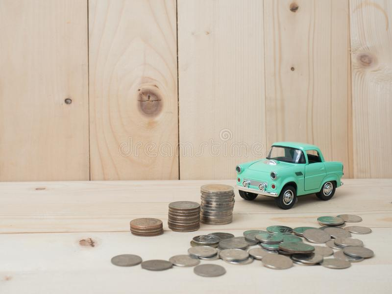 Oney coins stack growing with green car on wood background. Business growth investment and financial concept ideas.Real estate in. Oney coins stack growing with royalty free stock images