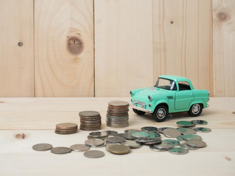Oney coins stack growing with green car on wood background. Business growth investment and financial concept ideas.Real estate in. Vestment. retro car and coins royalty free stock image