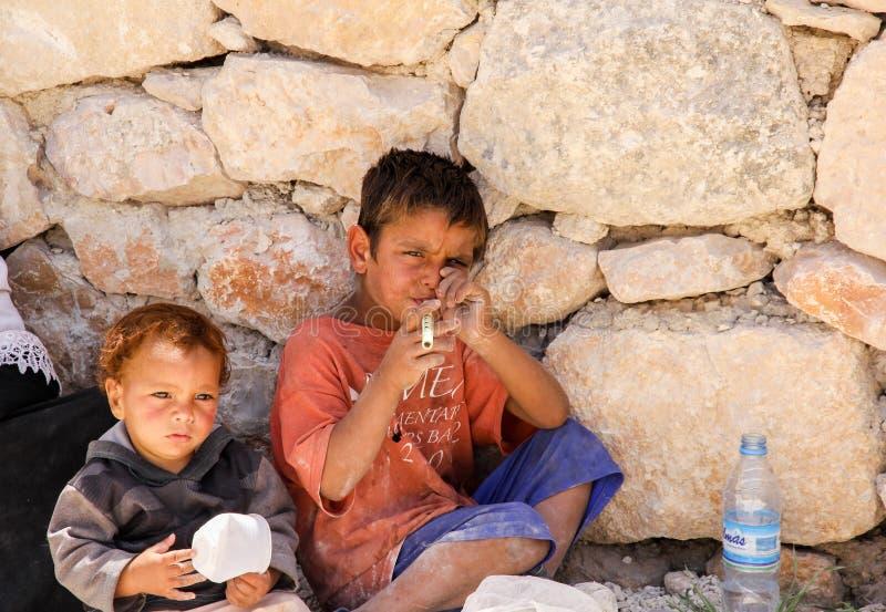 Ong-pojke som spelar bambuflöjten med hans yngre bror, Jerash, Jordanien royaltyfri bild