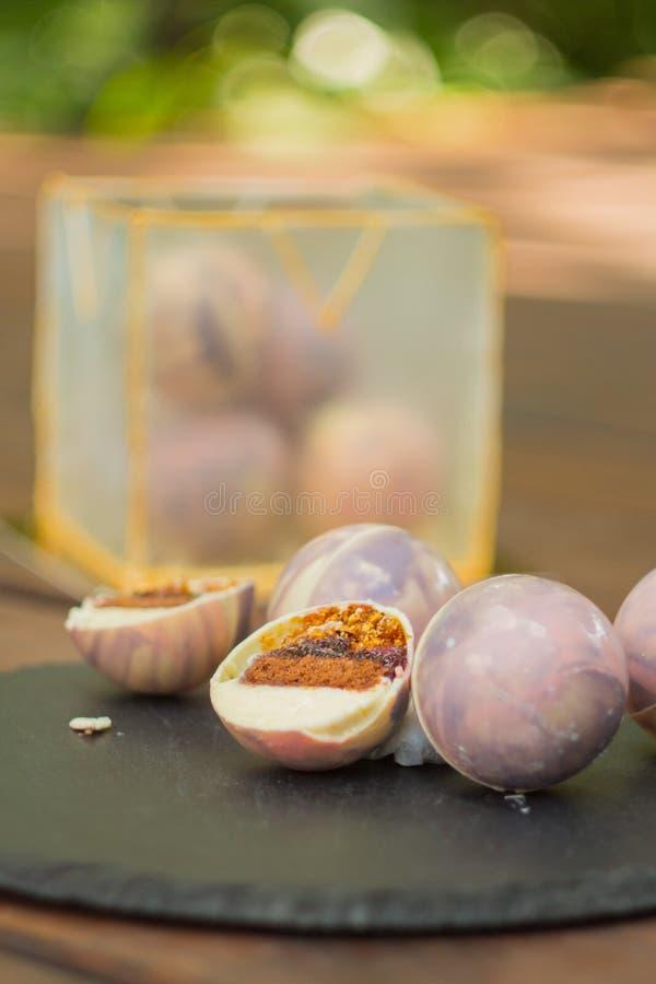 Ongebruikelijke cake in chocoladeballen en isomalt kubus Elke kom bevat okkernoot, brownies, praline stock afbeeldingen