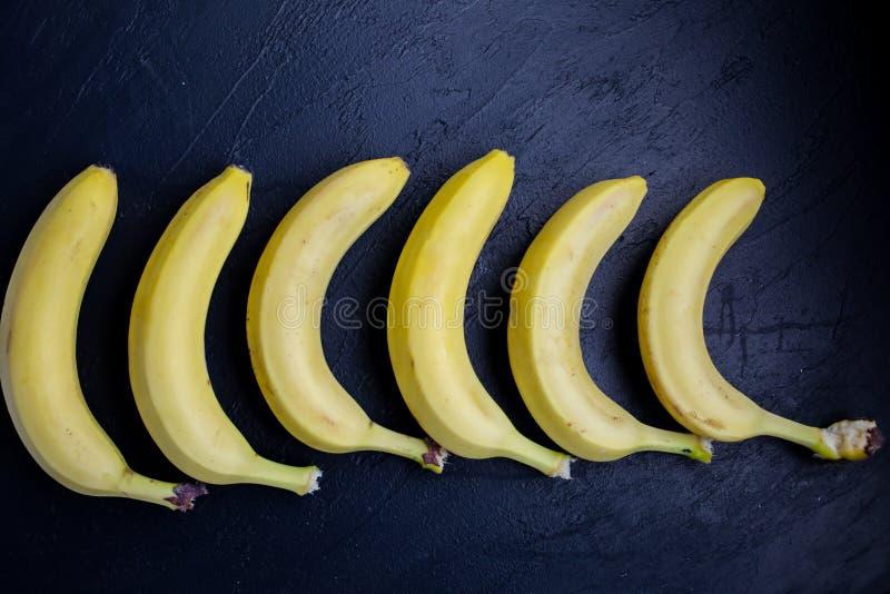 Ongebruikelijke en verse foto van bananen die op een rij op zwarte achtergrond liggen stylish royalty-vrije stock foto's