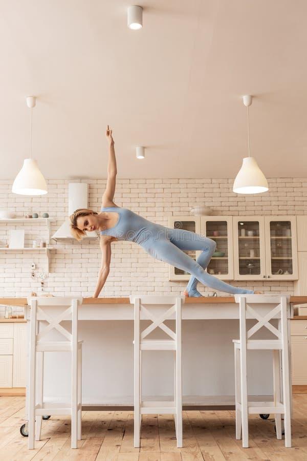 Ongebruikelijke magere jonge uitvoerder die op keukenlijst dansen royalty-vrije stock afbeelding