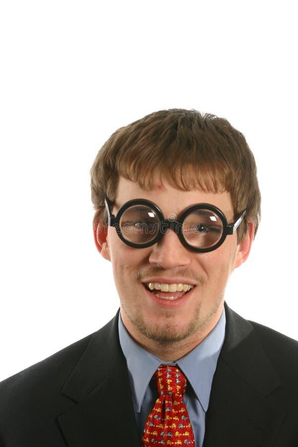 Ongebruikelijke uitdrukking met glimlach op de mens met dikke glazen in pak stock afbeelding
