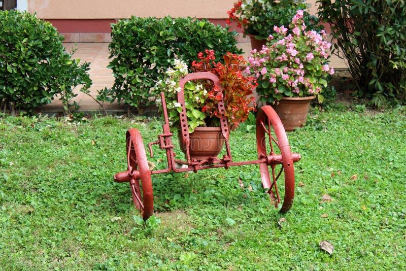 Ongebruikelijke uitstekende retro tuindecoratie met verschillende die grootte van wielen die worden gebruikt om bloempotten met v royalty-vrije stock afbeeldingen