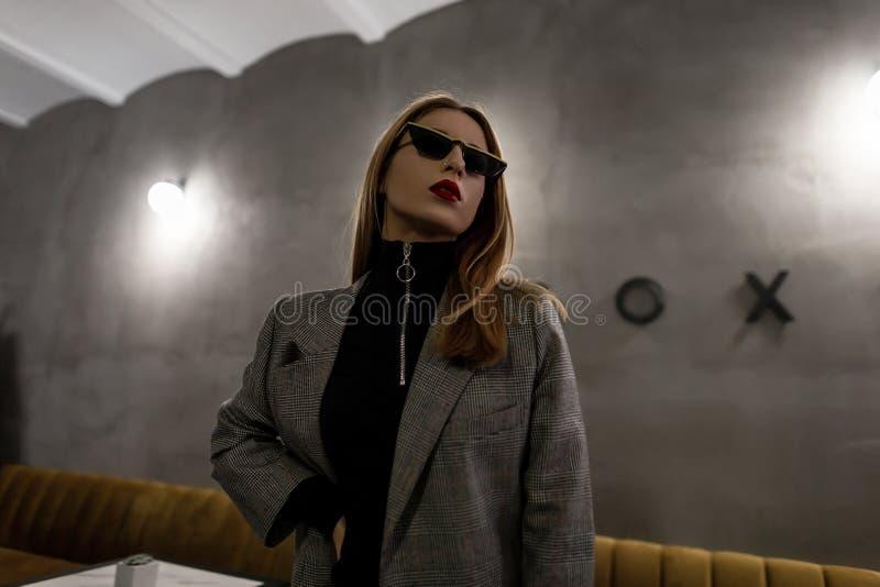 Ongebruikelijke verbazende jonge hipstervrouw in in geruit jasje in retro stijl in in zonnebril met doordrongen neus met rode lip royalty-vrije stock fotografie