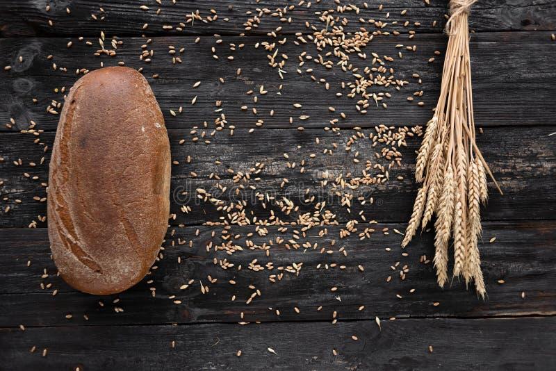 Ongedesemd brood op een houten lijst stapel van rijpe tarwe royalty-vrije stock afbeelding