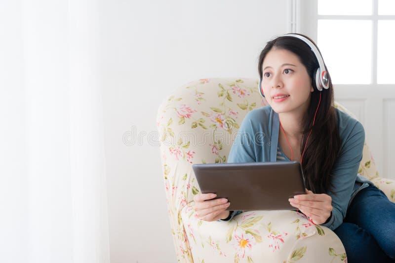 Ongehaaste dame die mobiele stootkussen het luisteren muziek gebruiken royalty-vrije stock afbeelding