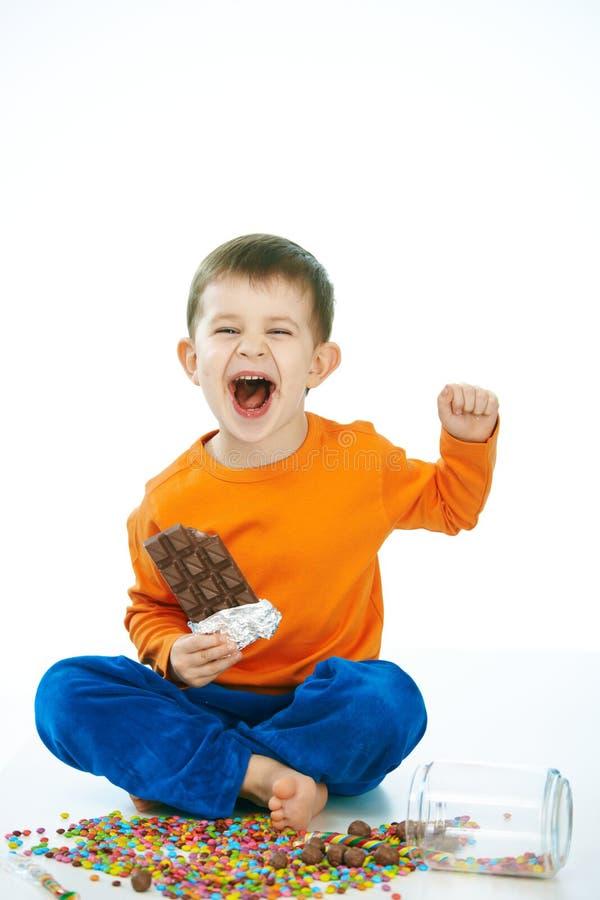 Ongehoorzaam jong geitje die chocoladezitting met de benen over elkaar eten stock foto
