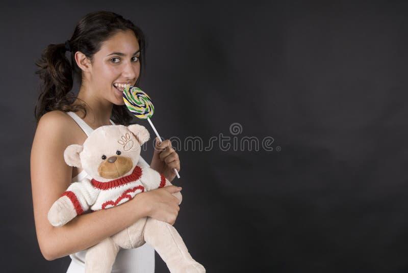 Ongehoorzaam meisje dat een grote pop lollie eet royalty-vrije stock afbeelding