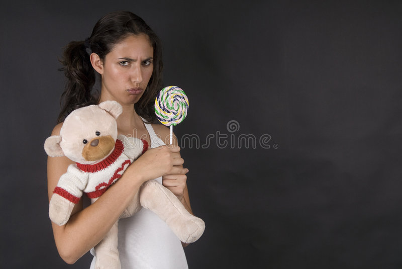 Ongehoorzaam meisje dat een grote pop lollie eet stock afbeeldingen