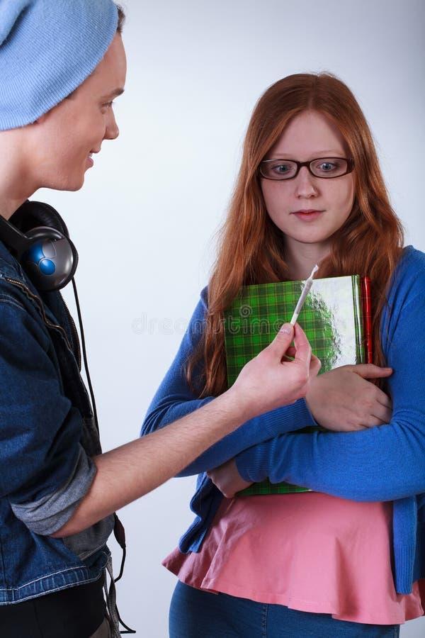 Ongehoorzame jongen die meisje een marihuanaverbinding geven royalty-vrije stock foto
