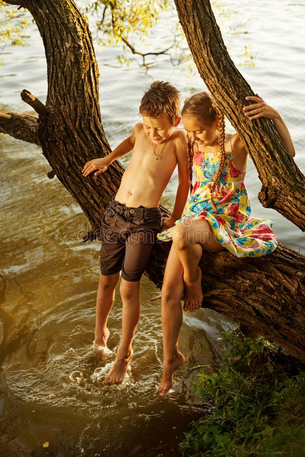 Ongehoorzame jongen en meisjeszitting op een tak over water, lachend, hebbend pret het spreken stock afbeelding