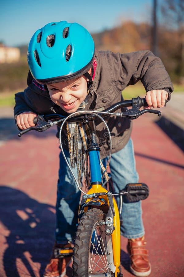 Ongehoorzame jongen met uitdagend gebaar over zijn fiets stock afbeeldingen