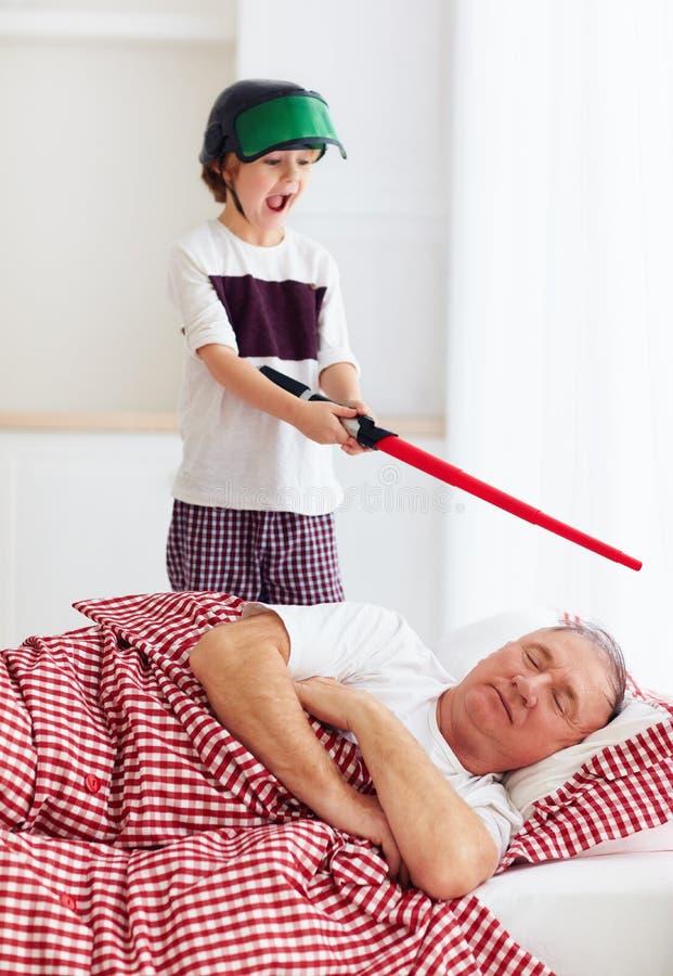 Ongehoorzame schreeuwende kleinzoon wekkende opa omhoog door rond binnen te spelen royalty-vrije stock afbeeldingen