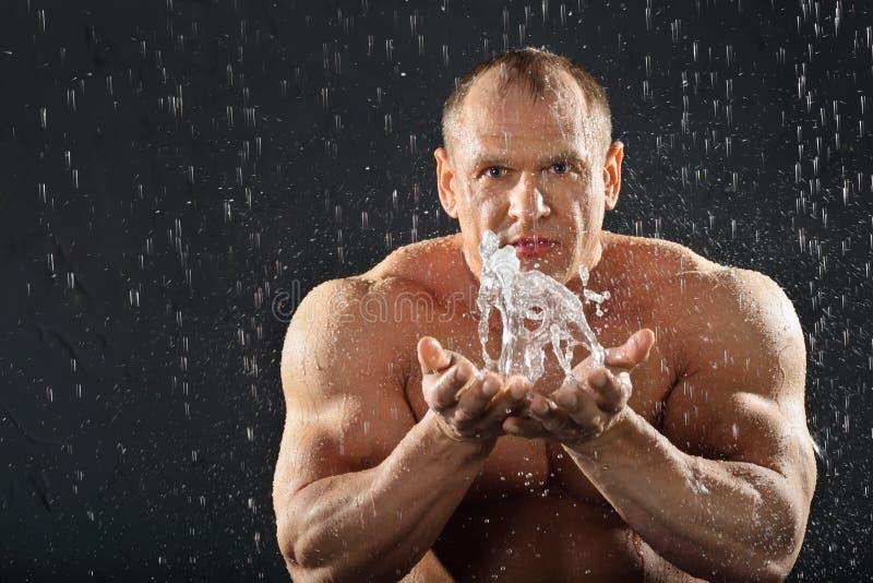 Ongeklede bodybuilder in regenplonsen van water stock foto's
