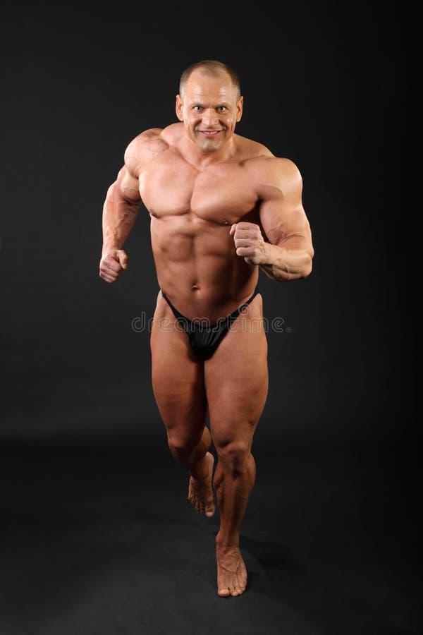 Ongeklede bodybuilderlooppas binnen studio royalty-vrije stock foto