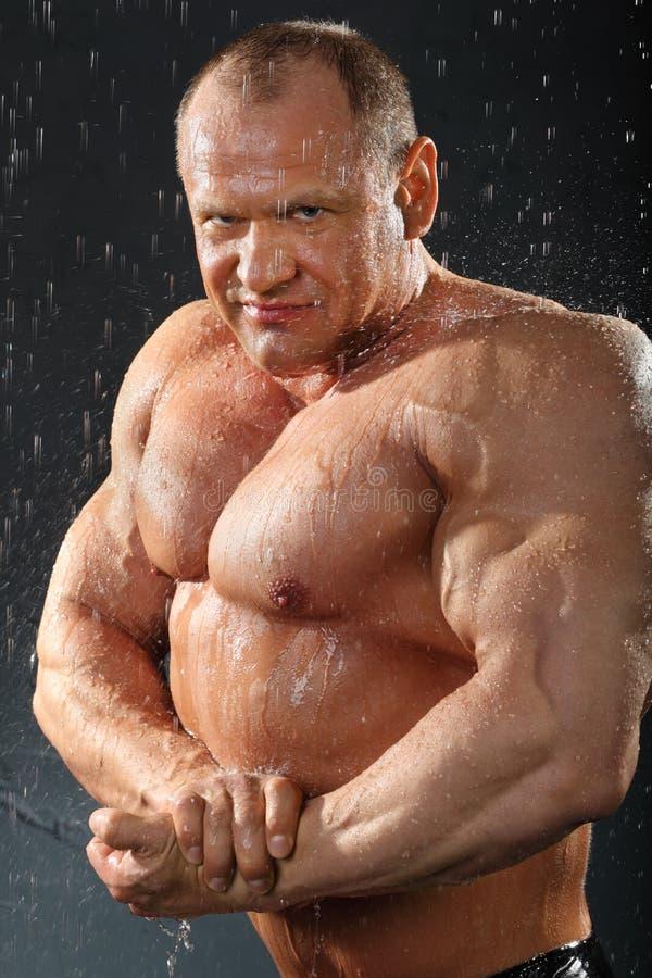 Ongeklede bodybuildertribunes in regen stock afbeelding