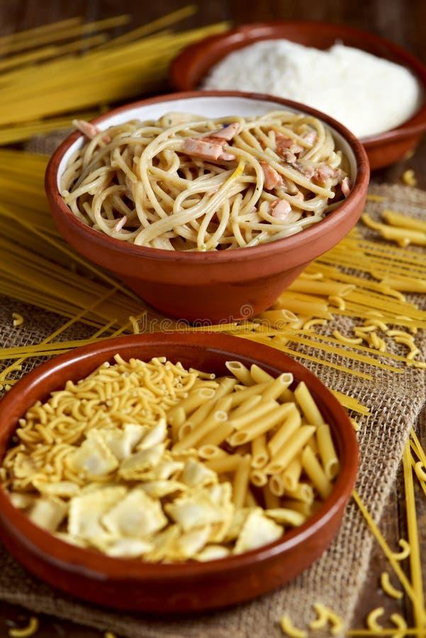 Ongekookte deegwaren, carbonara van spaghettialla en geraspte kaas stock foto